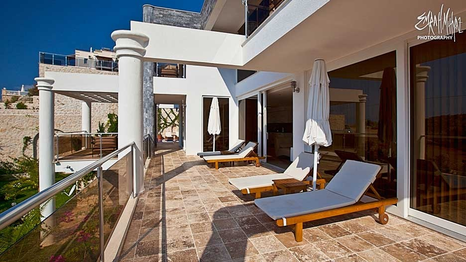 Large terrace with sunbeds extends the full length of the villa