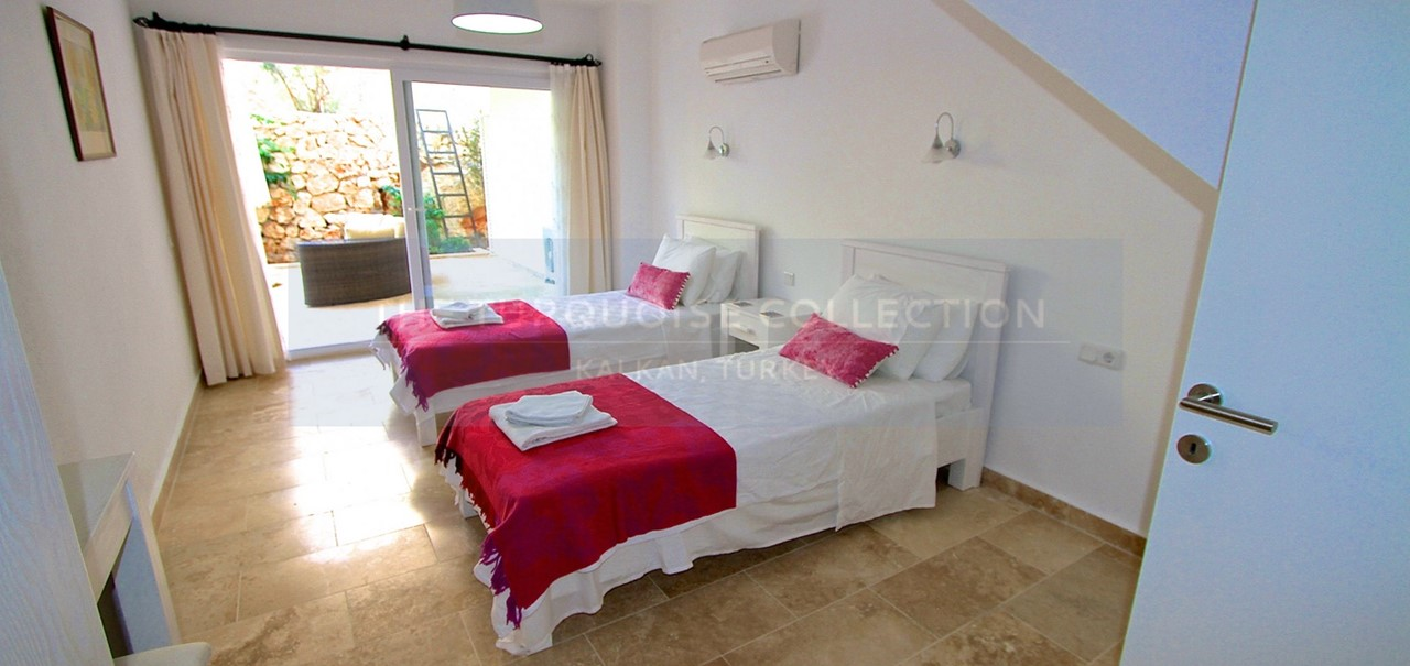 Spacious twin bedroom with doors to the lower terrace
